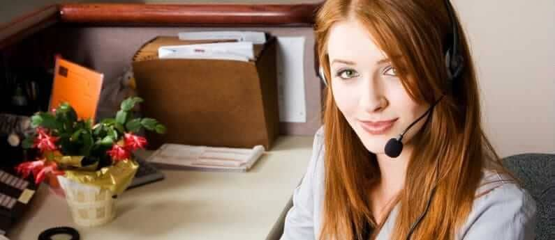 A Medical Office Receptionist sitting at her desk with a phone headset.