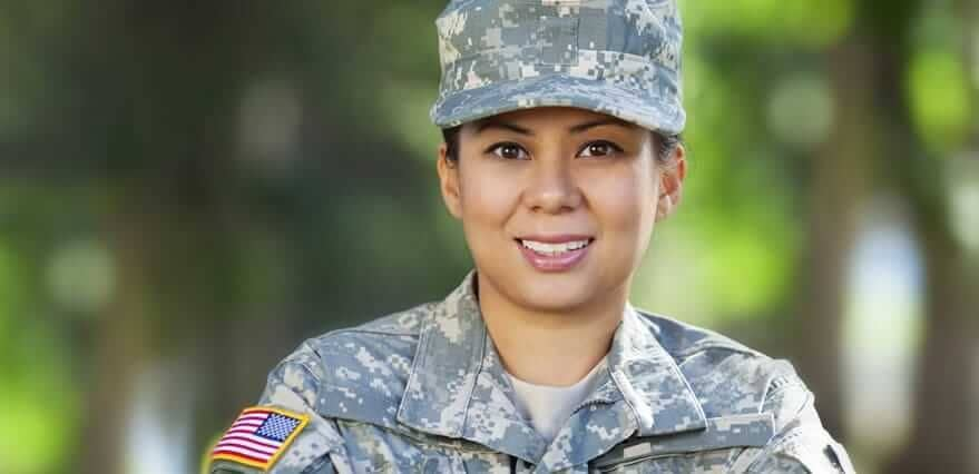 Close-up of veterans. She is smiling and wearing army fatigues.
