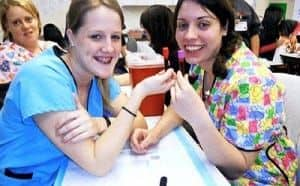 Two women in scrubs holding a vial of blood