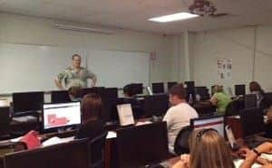 A man standing at the front of a classroom full of students at computers