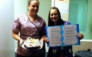 A woman holding a signboard and a woman holding a birthday cake