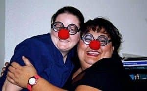 Two woman smiling with red clown noses on their faces