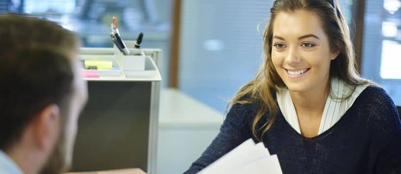 Woman smiles at man across from her at desk in an office setting.