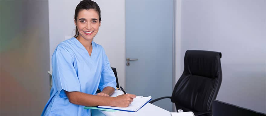 Female medical assistant writing notes at a desk.
